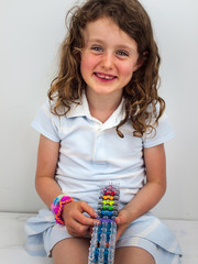 small smiling girl  with a band loom