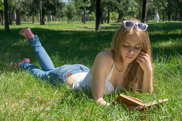 Girl holding a red apple and reading a book in a summer park