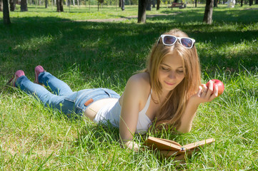 Girl holding a red apple and reading a book in a summer