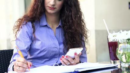 Businesswoman working with smartphone and documents in cafe