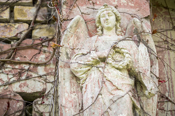 old angel sculpture with  peeling off paint