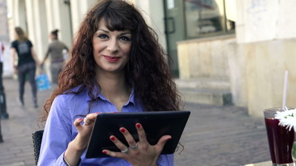 Happy attractive businesswoman with tablet computer in cafe