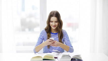 smiling student girl with smartphone and books