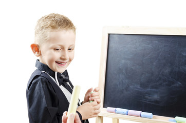 young boy stands at the blackboard with chalk