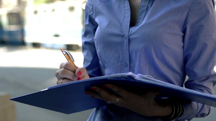 Young businesswoman working with documents in the city