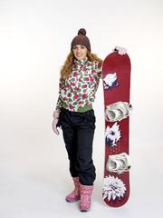 Joven mujer preparandose para la práctica de  snowboard.