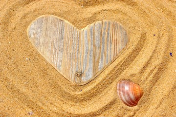 Single wooden love heart and seashell in the sand