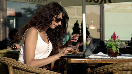 Woman doing online shopping on laptop in cafe