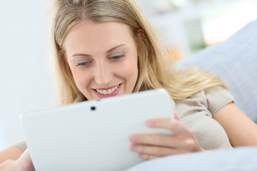Blond woman at home using digital tablet