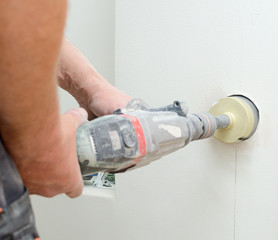 Man with Hammer drill doing hole for socket.
