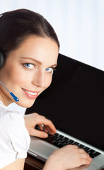 Phone operator in headset with laptop, at office