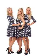 three girls in dot dresses and black shoes