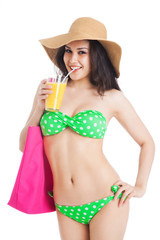 brunette girl in green swimsuit and hat, holding  glass of juice