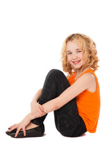 little smiling girl in orange clothes sitting on the floor