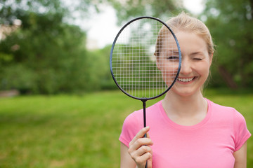 blonde girl holding tennis -racket wearing pinck t-shirt