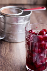 fresh pitted cherries in a glass, steel cup