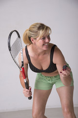 Woman in sports bra and green shorts playing squash
