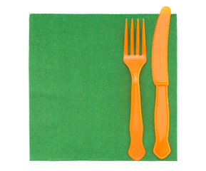 Picnic plastic cutlery on green serviette, napkin. Isolated on w