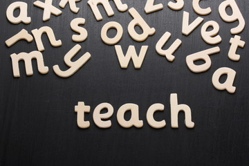 Wooden letters spell teach on a blackboard