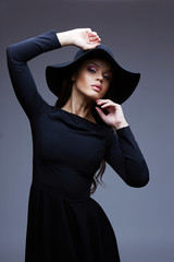 fashion portrait of elegant woman in black hat and dress