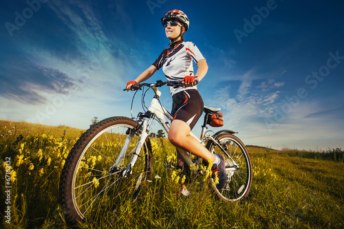 Woman is riding bicycle outside in the field - 67162132