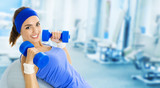 Fototapety Young happy woman doing fitness exercise, at gym
