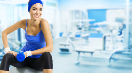 Young happy woman doing fitness exercise, at gym