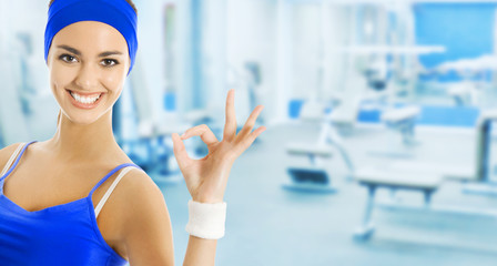 Young happy woman in sports wear gesturing, at gym
