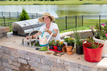 Retired senior woman gardening, in a brick patio
