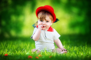 Happy little baby in red hat having fun in the park on solar gla