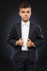 serious boy adjusts his black suit
