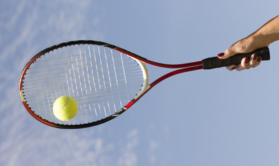 Tennis racquet and ball against blue sky