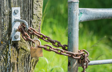 Rusty chain and a closed hardened padlock from close