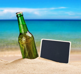 Beer bottle in the sand on the beach and a blackboard