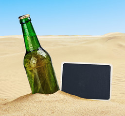Beer bottle in the sand in the desert and the blackboard