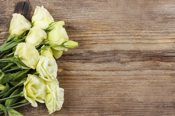 Bouquet of eustoma flowers on wooden table.