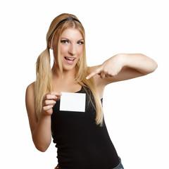 lachende hübsche Frau zeigt auf leere Visitenkarte