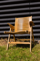 wooden chair on grass in front of black wall