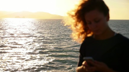Woman Sending Text Message from her Phone against Sea View.