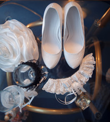 white bridal shoes and other wedding attributes on a table