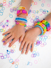 childs arms wearing multicoloured bracelets