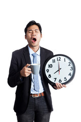 Asian office man yawn with a clock and a cup of coffee