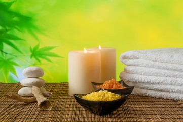Spa massage with towel stacked, candle and sea salt