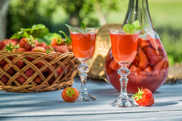 Homemade strawberry liqueur served in the garden