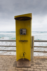 yellow phone booth on the sea background