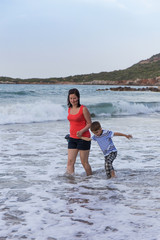 mother and son walking along the seashore