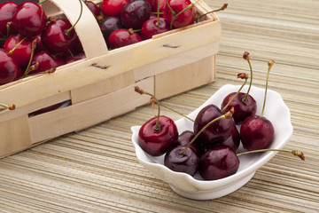 cherries in the basket and bowl on the bamboo mat