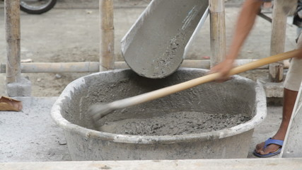 Worker put cement/Workers put in a bucket of cement.