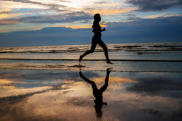 Silhouette and reflection of woman running on sunset beach