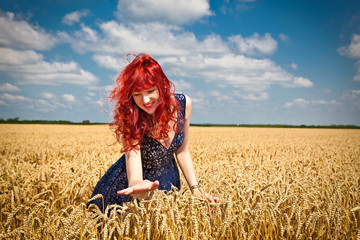 Happy woman in golden wheat.